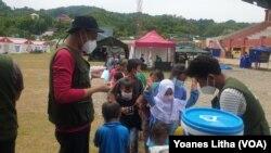 Relawan IBU Foundation membagikan masker untuk anak-anak di shelter terintegrasi Kementerian Sosial RI di Stadion Manakarra, Mamuju Sulawesi Barat, Minggu (31/1/2021). (Foto: VOA/Yoanes Litha)