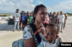 People injured or affected by the earthquake and tsunami wait to be evacuated on an air force plane in Palu, Central Sulawesi, Indonesia, Sept. 30, 2018.
