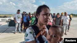 Warga yang luka-luka akibat gempa dan tsunami menunggu untuk dievakuasi dengan pesawat di Palu, Sulawesi Tengah, 30 September 2018. (Antara Foto/Muhammad Adimaja via REUTERS)