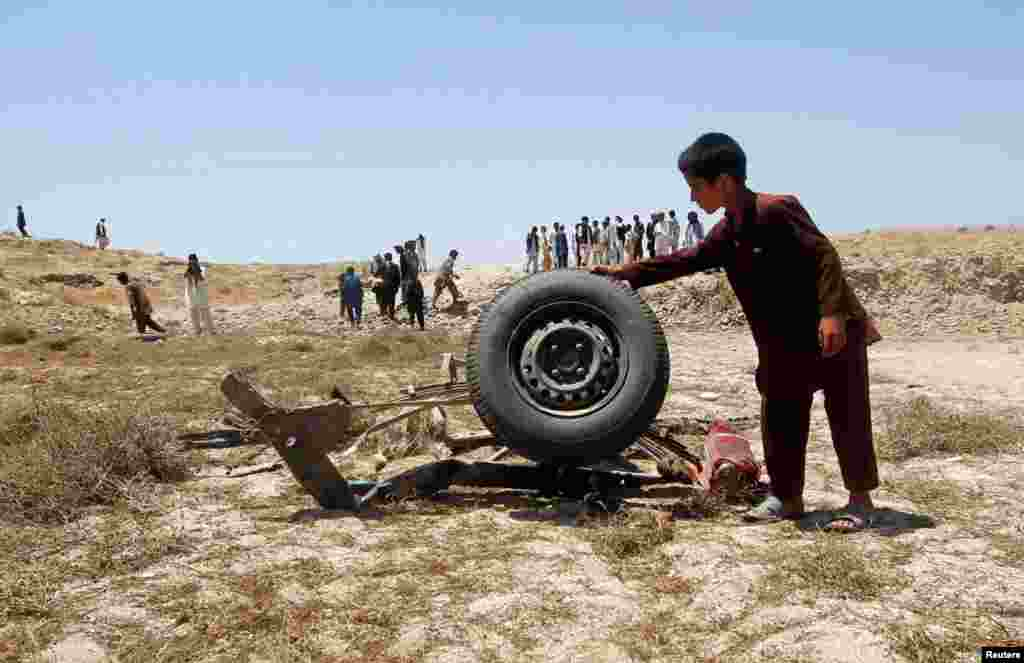 Afghan villagers stand at the site of a roadside bomb in Laghman province June 3, 2013.