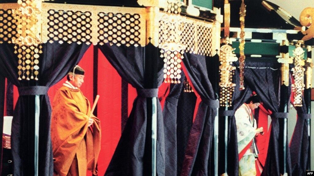 """Dalam foto 12 November 1990, Kaisar Akihito (kiri) mengenakan busana tradisional Jepang berdiri di dalam """"takamikura"""" (takhta kerajaan) dalam upacara penobatan di Istana Kekaisaran Jepang. (Foto: AFP/Arsip)"""
