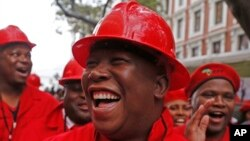 FILE - Julius Malema, center, leader of the Economic Freedom Fighters (EFF), arrives at Parliament wearing a hard hat and overall to show solidarity with coal mine workers, in Cape Town, South Africa, May 21, 2014.