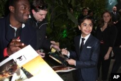 "Actor Neel Sethi, who plays the character Mowgli, signs autographs upon arrival at the premiere of the film ""The Jungle Book"" in London, April 13, 2016."