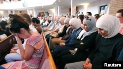 FILE - People from different faiths pray during an interfaith vigil for the victims of the Tennessee shooting, at Olivet Baptist church in Chattanooga, Tennessee, July 17, 2015.