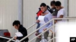 Familias inmigrantes abandonan una instalación de Inmigración y Control de Aduanas de EE.UU. después de reunirse en San Antonio, el 11 de julio de 2018.