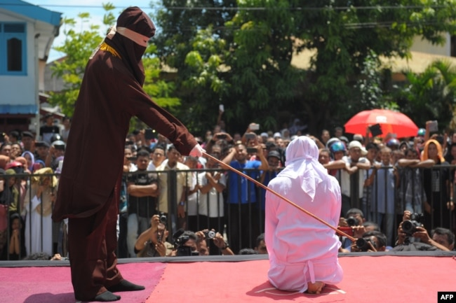 A religious officer canes an Acehnese youth onstage as punishment for dating outside marriage, which is against Sharia, or Islamic law, outside a mosque in Banda Aceh, Aug. 1, 2016. The strictly Muslim province, Aceh has become increasingly conservative in recent years and is the only one in Indonesia implementing Sharia.