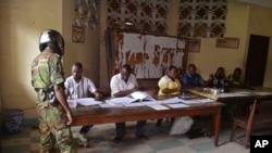 Un soldat Congo ( l), dans un bureau de vote , à Brazzaville , au Congo . Le président de la République sortant a gouverné le pays d'Afrique centrale depuis plus de 30 ans , devrait faire une croisière à une réélection dimanche,cinq mois après un référendum constitutionnel supprimé la limitation du mandat et l'âge qui aurait barré l'âge a 72 de M. Sassou Nguesso. (AP Photo / John Bompengo )