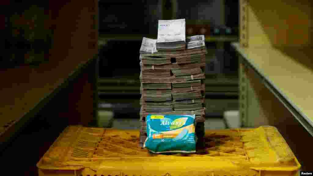 Un paquete de toallas sanitarias junto a 3.500.000 bolivars, equivalente a 0,53 dólares.