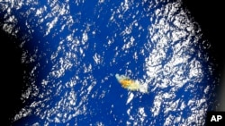 An image taken onboard a Royal New Zealand P-3 Orion shows a piece of unknown debris floating just under the water while the plane was searching for missing Malaysia Airlines Flight MH370 in the southern Indian Ocean, Australia, March 31, 2014.