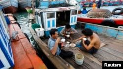 Ngư dân ăn trên tàu trước khi xuất bến trên đảo Lý Sơn, tỉnh Quảng Ngãi, ngày 1 tháng 7, 2014.