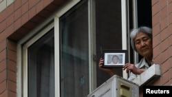 """资料照:""""天安门母亲群体""""其中代表人物张先玲在住宅窗口展示八九六四在天安门被军队杀死的儿子的照片。"""