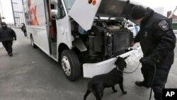 Cảnh sát và chó nghiệp vụ khám xét một chiếc xe trên đường phố gần tòa án liên bang ở Boston, ngày 3/3/2015.