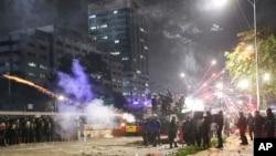 Polisi anti huru-hara menembakkan gas air mata dalam aksi demonstrasi mahasiswa di luar gedung DPR/MPR di Senayan, Jakarta, Selasa (24/9).