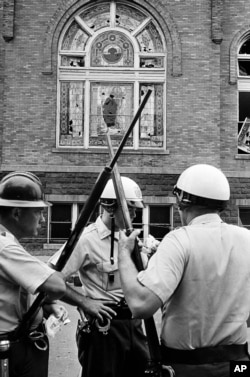 Policeman stand guard outside the 16th Street Baptist Church in Birmingham, Ala., which was the scene of an explosion that killed four African American children, Sept. 15, 1963.