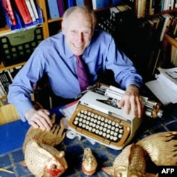 In this photo from 1998, publisher Barney Rosset poses with some of his favorite things in his New York apartment