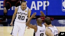 San Antonio Spurs guard Manu Ginobili (20), guard Patty Mills (8) and center Tiago Splitter (22) celebrate against the Miami Heat during the second half in Game 5 of the NBA basketball finals on Sunday, June 15, 2014.