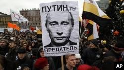 """俄罗斯反对派的支持者在圣彼得堡举行示威,抗议议会选举舞弊和现政府政策,标语上写着:""""普京,你是叛徒。"""""""