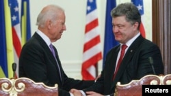FILE - U.S. Vice President Joe Biden (L) shakes hands with Ukraine's President Petro Poroshenko during a news conference in Kyiv, November 2014.