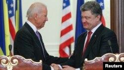 U.S. Vice President Joe Biden (L) shakes hands with Ukraine's President Petro Poroshenko during a news conference in Kyiv, Nov. 21, 2014.