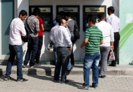 People line in front of automated teller machines (ATMs) in Hatay, May 17, 2013.