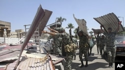 Egyptian Army soldiers clear away scrap metal used by protesters during clashes outside the Ministry of Defense in Cairo, Egypt, May 5, 2012.