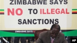 FILE: Zimbabwean President Robert Mugabe signs a petition against Western economic sanctions targeting his supporters, in Harare, Wednesday, March, 2, 2011.
