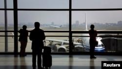 FILE - Passengers wait to board their plane at Shanghai's Hongqiao International Airport.