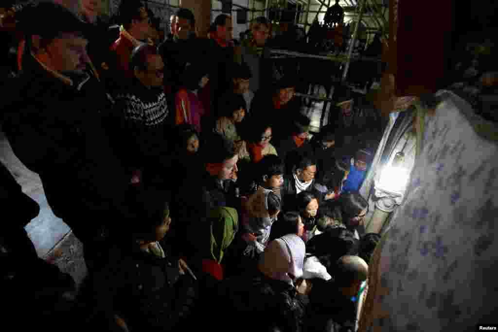 Para pengunjung menunggu di dalam gua, tempat yang dipercaya sebagai lokasi di mana Santa Perawan Maria melahirkan Yesus pada hari Natal, di dalam gereja kuno Nativity di Tepi Barat, Bethlehem, 25 Desember 2016.