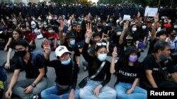 Pro-democracy demonstrators flash a three-finger salute while sitting on the ground during a Thai anti-government mass protest, on the 47th anniversary of the 1973 student uprising, in Bangkok, Thailand October 14, 2020. REUTERS/Soe Zeya Tun