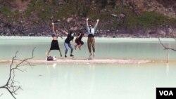 Empat wisatawan mancanegara melompat untuk foto di Kawah Putih, Ciwidey, Kabupaten Bandung Barat, Jawa Barat. (VOA/Rio Tuasikal)