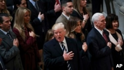 President Donald Trump signs the National Anthem during a National Prayer Service at the National Cathedral, in Washington, Jan. 21, 2017.