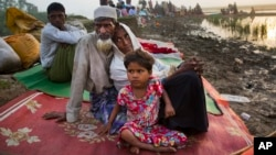 Rohingya man Nur Ahmad, 70, his wife Lalu Bibi and their grand daughter Ashuka Bibi, 5, who crossed over to Bangladesh the previous day, wait for permission to go to the refugee camps after spending the night in the rice fields near Palong Khali, Bangladesh, Nov. 2 2017. It took them nine days to reach the border since they left their family home at Buthi Dawng district.