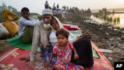 Rohingya man Nur Ahmad, 70, his wife Lalu Bibi and their grand daughter Ashuka Bibi, 5, who crossed over to Bangladesh the previous day, wait for permission to go to the refugee camps after spending the night in the rice fields near Palong Khali, Bangladesh.