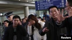 失踪马航班机MH370上的乘客亲属在北京首都机场焦急和哀伤地等待亲人消息。(2014年3月8日)