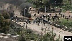 Para demonstran berkumpul dekat sebuah barikade di Dara'a, Suriah, Jumat (8/4).