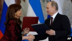Russian President Vladimir Putin and Argentina's President Cristina Fernandez exchange documents at a signing ceremony in the Kremlin in Moscow, April 23, 2015.