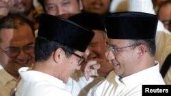 Anies Baswedan dan Sandiago Uno berbincang setelah perhitungan suara pemilihan Gubernur DKI Jakarta. (REUTERS/Beawiharta)