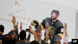 Vegas Golden Knights defenseman Shea Theodore gives his stick to fans after the Knights defeated the Washington Capitals 6-4 in Game 1 of the NHL hockey Stanley Cup Finals Monday, May 28, 2018, in Las Vegas. (AP Photo/Ross D. Franklin)