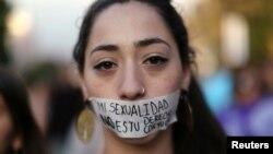 """在智利圣地亚哥举行的声援""""消除对妇女暴力国际日""""的示威活动中,一名妇女用一块胶带把嘴封住,胶带上面写着""""我的性别不等于你的配偶同居权。"""" (2016年11月25日)"""
