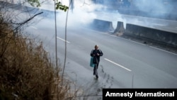 A pedestrian takes cover from clouds of tear gas fired by the Bolivarian National Police during clashes at an anti-government protest in Caracas, Venezuela, March 20, 2014.