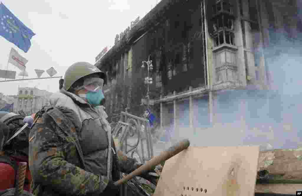 Người biểu tình chống chính phủ đứng sau một chướng ngại vật trong cuộc đụng độ với cảnh sát chống bạo động tại Quảng trường Độc lập ở Kiev, Ukraina, ngày 19/2/2014.