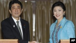 Japanese Prime Minister Shinzo Abe, left, poses with his Thai counterpart Yingluck Shinawatra for photographers at the end of a news conference at the Government House in Bangkok, Thailand, January 17, 2013.