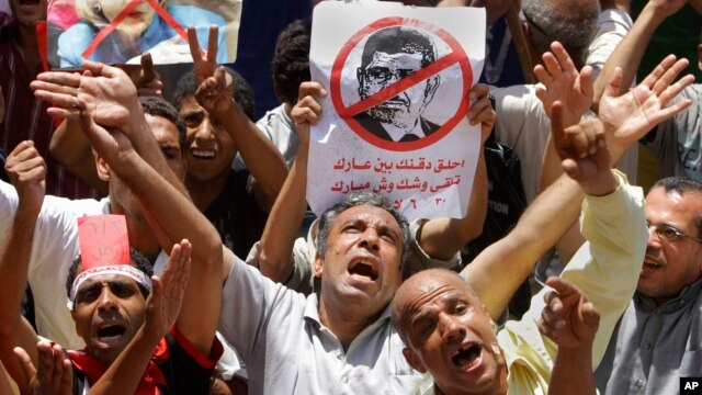 Egyptian protesters shout anti-Muslim Brotherhood slogans as they hold posters depicting U.S. Ambassador to Egypt Anne Patterson and President Mohammed Morsi during a protest in Tahrir Square in Cairo, Egypt, June 28, 2013.