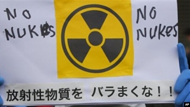 A protester in protective mask holds a placard during an anti nuclear rally in Tokyo, Sunday, March 27, 2011
