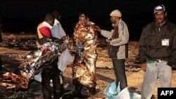 Di dân Libya được giúp đỡ khi đặt chân đến hòn đảo ở Lampedusa, Italia, sáng chủ nhật, ngày 8/5/2011
