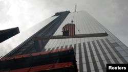 Una viga con la bandera de Estados Unidos es colocada en lo alto de la torre 4 del World Trade Center, en Nueva York.
