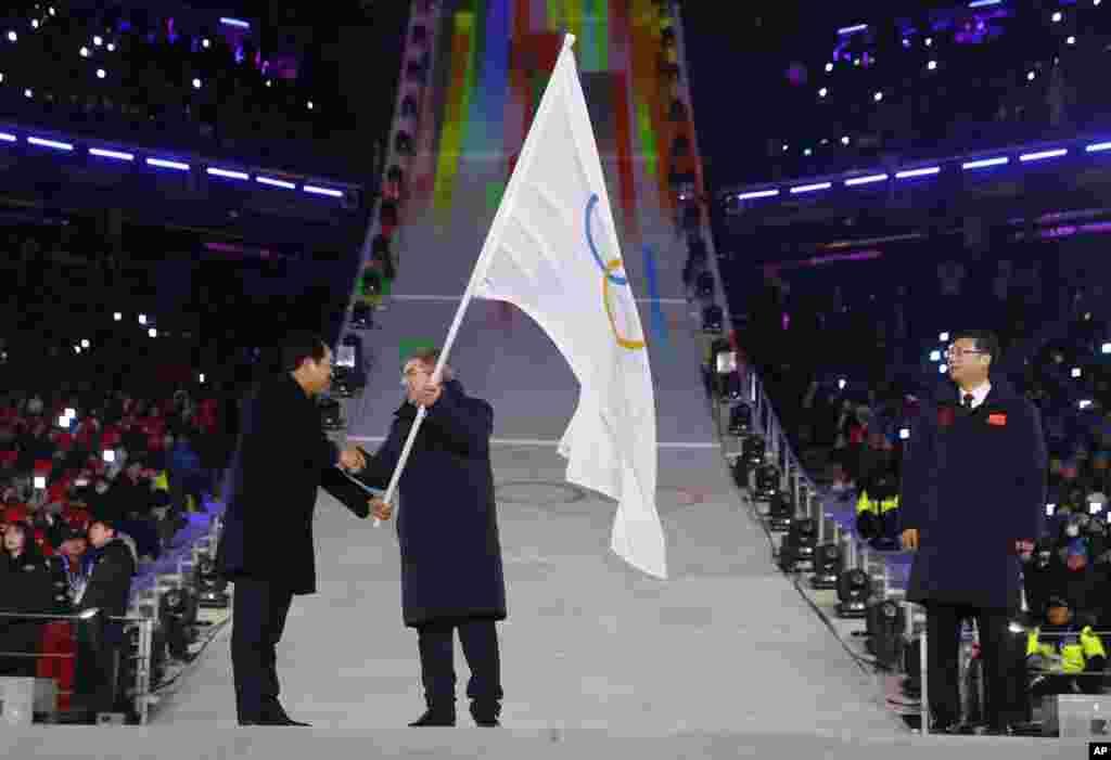 El presidente del Comité Olímpico Internacional, Thomas Bach, en el centro, recibe la bandera olímpica de Sim Jae-guk, a la izquierda, del alcalde de Pyeongchang, durante la ceremonia de clausura de los Juegos Olímpicos de Invierno de 2018, el 25 de febrero de 2018.