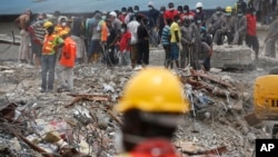 Des employés cherchent des survivants après l'effondrement d'un immeuble à Lagos, Nigeria, septembre 2014. Image : AP