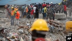 FILE - Rescue workers are seen on the site of a collapsed building in Lagos, Nigeria, Sept. 16, 2014.