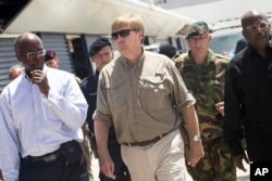 This photo provided by the Dutch Defense Ministry shows Dutch King Willem-Alexander, center, visiting after the passing of Hurricane Irma, in Dutch Caribbean St. Maarten, Sept. 11, 2017.